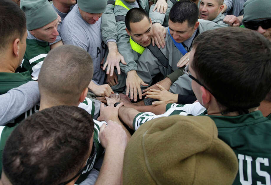 U.S. soldiers put their hands together before a football game to mark Thanksgiving at the U.S.-led coalition base in Kabul, Afghanistan, Thursday, Nov. 22, 2012. (AP Photo/Musadeq Sadeq) / AP