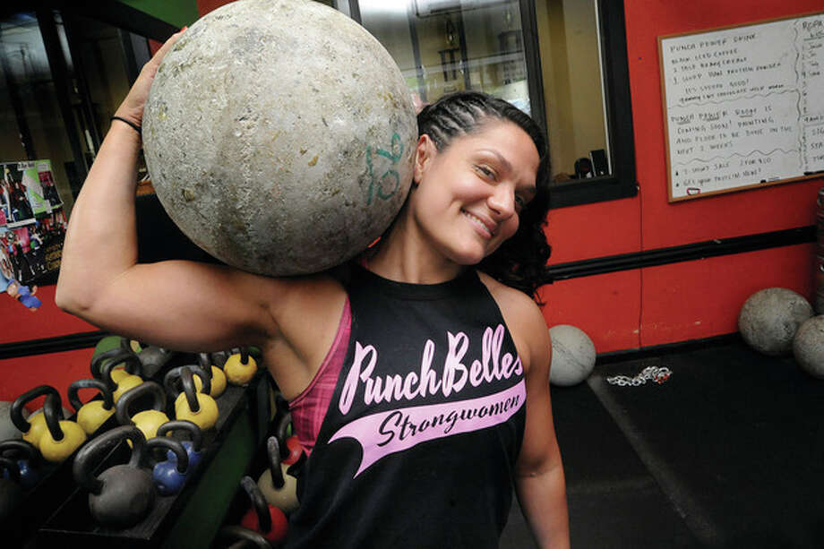 Hour photos / Matthew VinciAbove, Norwalk's Punch Kettlebell owner Stefanie Tropea balances a 90-pound Atlas Stone on her shoulder. She will compete in the America's Strongest Woman competition Oct. 18 to 19 in Denison, Texas. Below, Tropea hoists a 100-pound log.