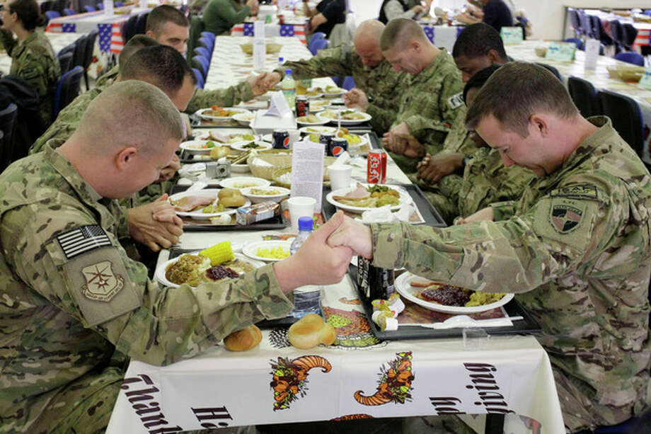 U.S. soldiers pray before eating a Thanksgiving meal at a dining hall at the U.S.-led coalition base in Kabul, Afghanistan, Thursday, Nov. 22, 2012. The dining hall at the U.S.-led coalition base in the Afghan capital served up mac-and-cheese along with traditional Thanksgiving Day fixings. (AP Photo/Musadeq Sadeq) / AP
