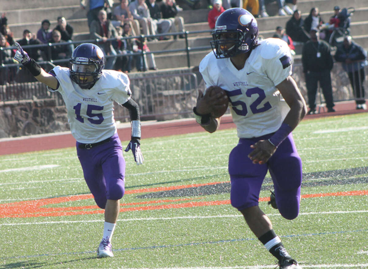 Westhill's Caleb Jones, right, races up the field with an interception return as teammate Davell Cotterell celebrates during the Vikings 20-6 win over Stamford.