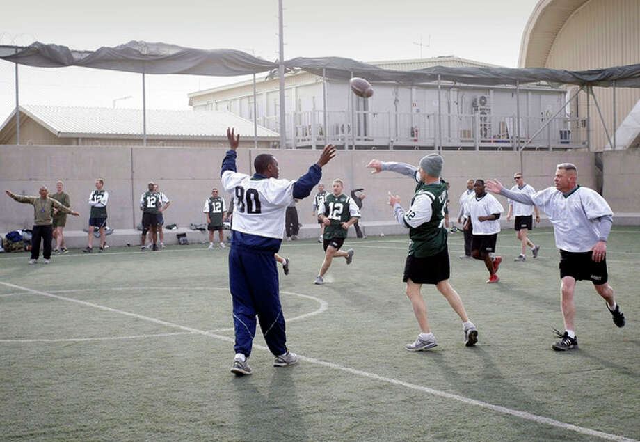 U.S. soldier play football to mark Thanksgiving at the U.S.-led coalition base in Kabul, Afghanistan, Thursday, Nov. 22, 2012. (AP Photo/Musadeq Sadeq) / AP