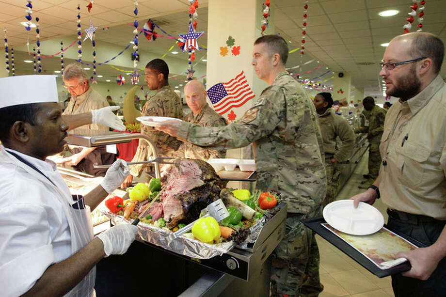 A dining facility worker, left, serves meat to soldiers and civilians for their Thanksgiving meal at the U.S.-led coalition base in Kabul, Afghanistan, Thursday, Nov. 22, 2012. The dining hall at the U.S.-led coalition base in the Afghan capital served up mac-and-cheese along with traditional Thanksgiving Day fixings. (AP Photo/Musadeq Sadeq) / AP