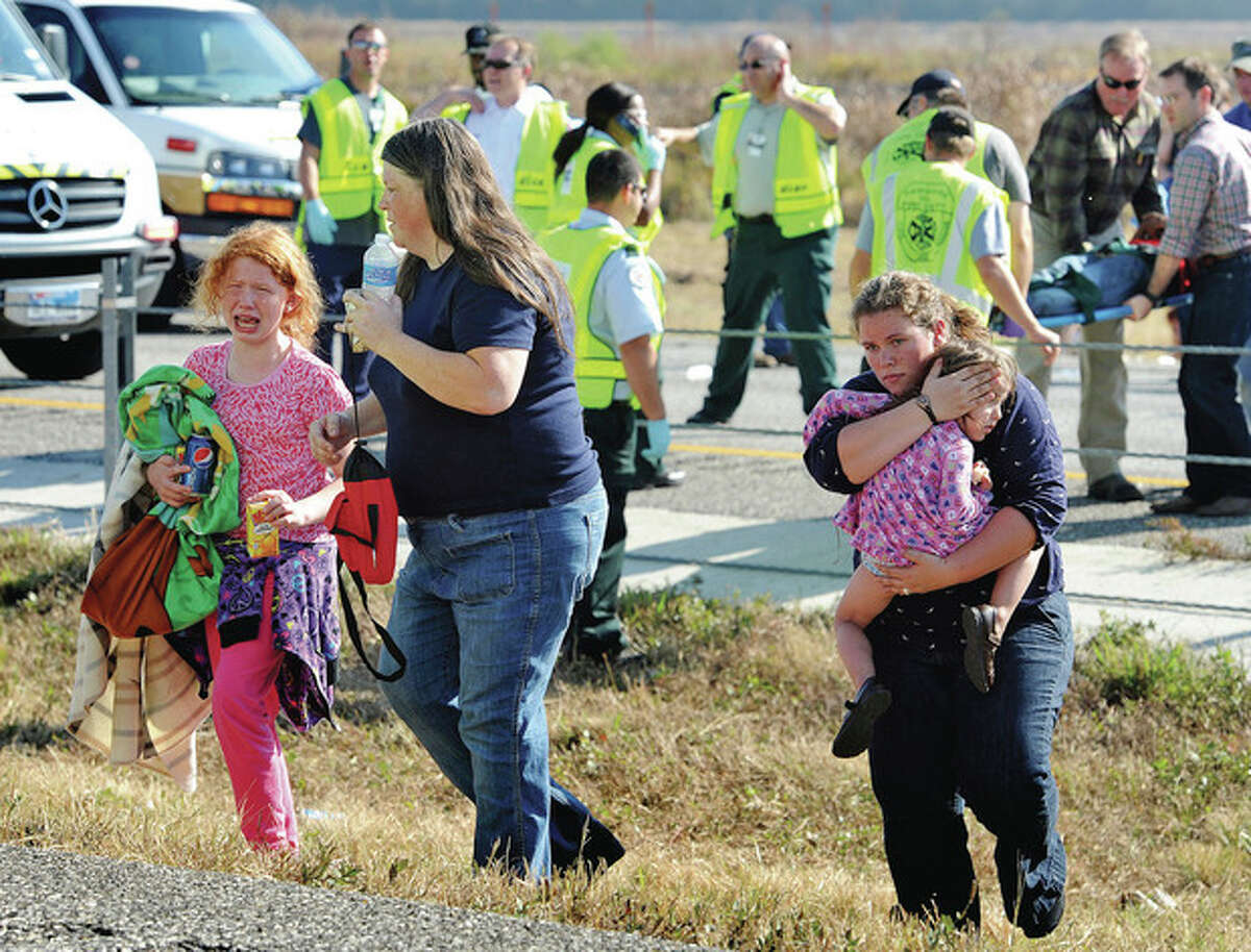 An family walks from the massive pile-up accident on Interstate 10 in Southeast Texas Thursday Nov. 22, 2012. The Texas Department of Public Safety says at least 35 people have been injured in a more than 50-vehicle pileup. (AP Photo/The Beaumont Enterprise, Guiseppe Barranco)