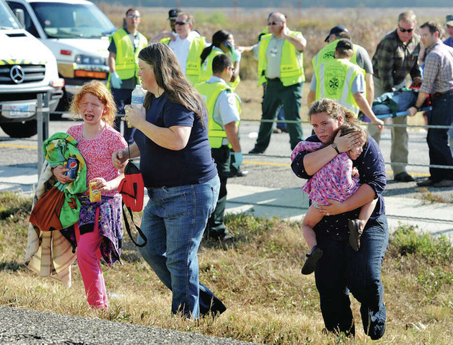 An family walks from the massive pile-up accident on Interstate 10 in Southeast Texas Thursday Nov. 22, 2012. The Texas Department of Public Safety says at least 35 people have been injured in a more than 50-vehicle pileup. (AP Photo/The Beaumont Enterprise, Guiseppe Barranco) / The Beaumont Enterprise