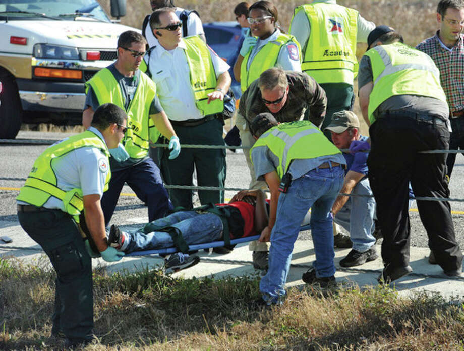 Emergency workers carry a victim across the Interstate 10 median after a massive auto accidentin Southeast Texas Thursday Nov. 22, 2012. The Texas Department of Public Safety says at least 35 people have been injured in a more than 50-vehicle pileup. (AP Photo/The Beaumont Enterprise, Guiseppe Barranco) / The Beaumont Enterprise