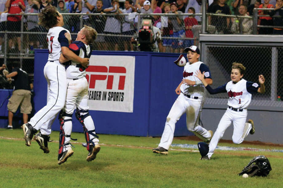 Westport's Pitcher Chad Knight leaps into the arms of Catcher Matt Stone as Matt Brown and Christopher Drbal run onto the field after Westport's 1-0 victory over Lincoln, R.I. in the Little League Baseball Eastern Regional State Championships on Saturday night at Giamatti Little League Field in Bristol, CT. (Hour Photo / Chris Palermo) / © 2013 Hour Newspapers All Rights Reserved