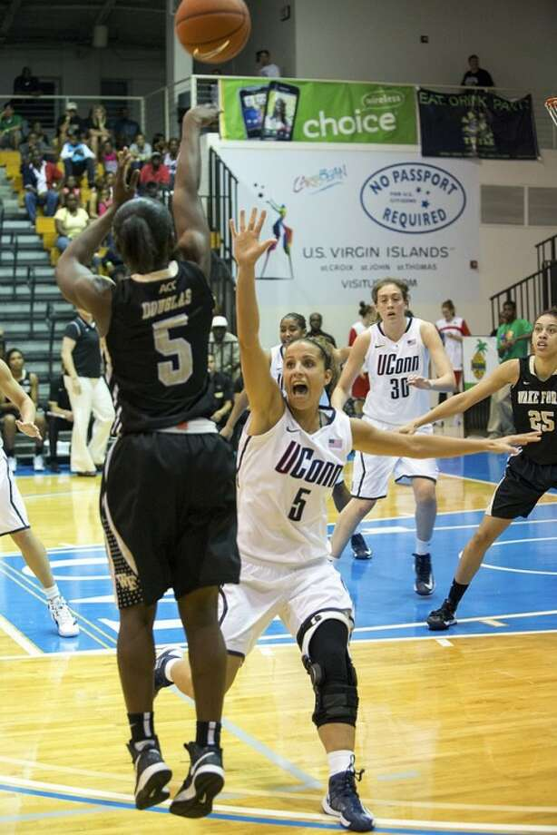 Connecticut's guard Caroline Doty, right, tries to block the shot of Wake Forest's guard Chelsea Douglas during the second half of an NCAA women's college basketball game in St. Thomas, U.S. Virgin Islands, Thursday, Nov. 22, 2012. Connecticut won 95-34. (AP Photo/Thomas Layer)