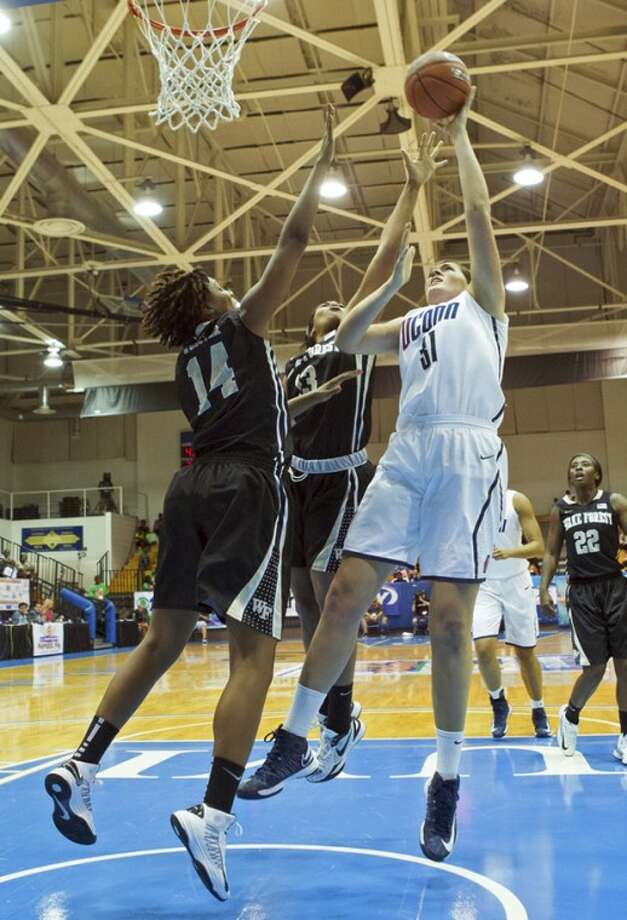 Connecticut's center Stephanie Dolson, right, shoots for the basket against pressure from Wake Forest's forwards Susie Webster, left, and Mykala Walker during the first half of an NCAA women's college basketball game in St. Thomas, U.S. Virgin Islands, Thursday, Nov. 22, 2012. (AP Photo/Thomas Layer)