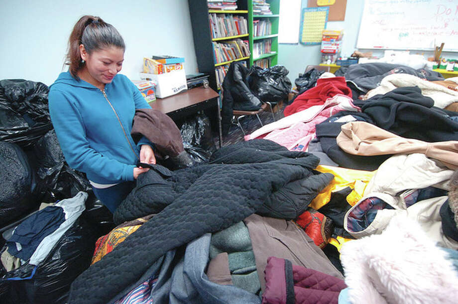 Hour Photo Alex von Kleydorff; Beatrice Lazaro looks for coats for her family during a coat give away at the SONO Community Thanksgiving dinner / 2012 The Hour Newspapers