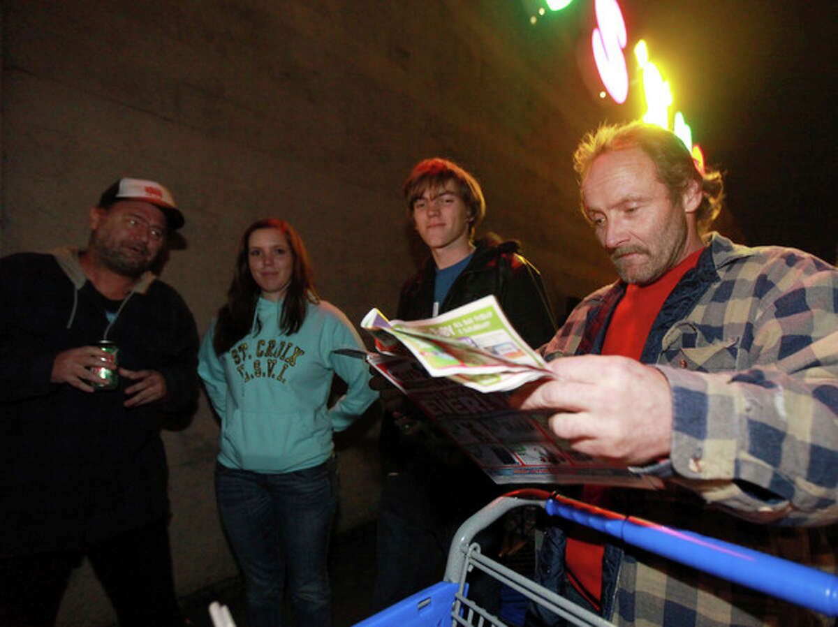 """Charles Collins, Lily Cry, 15, Justin Collins, 17, and John Nelson (left to right) wait in a line outside of Toys """"R"""" Us formed before its opening at 8 p.m. as shoppers took advantage of the sales and deals in the earlier shopping period for the typical """"Black Friday"""" event on Thursday evening, Nov. 22, 2012 in Chico, Calif. (AP Photo/Jason Halley, Chico Enterprise-Record)"""