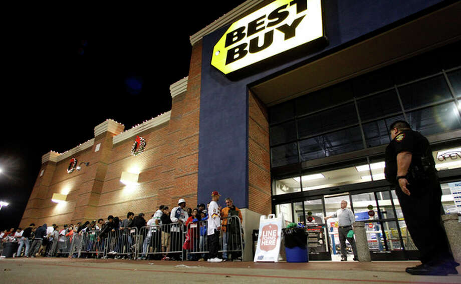Tarrant County Sheriffs Deputy Nick Downs, right, watches a line of shoppers as Best Buy general manager Shaun Ogdie, standing at door, peers outside as he and his employees prepare to open at midnight Thursday Nov. 22, 2012, in Arlington, Texas. (AP Photo/Tony Gutierrez) / AP