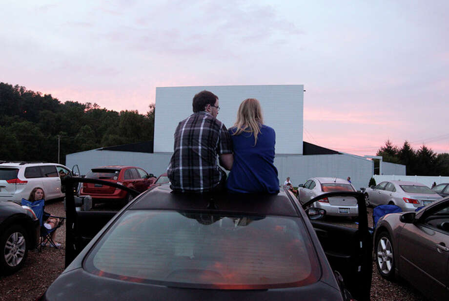 In this July 20, 2013 photo, Alex Lockhart, left, and Mikayla Green, both of Newark, watch the sunset while waiting for the movie to start at the Skyview drive-in theater in Lancaster, Ohio. The Skyview was the first drive-in theater in Ohio to convert to a digital projector. The latest threat to the existence of drive-in theaters is the conversion from 35mm film to digital prints and the expense involved in converting projectors to the new format. (AP Photo/Jay LaPrete) / FR52593 AP