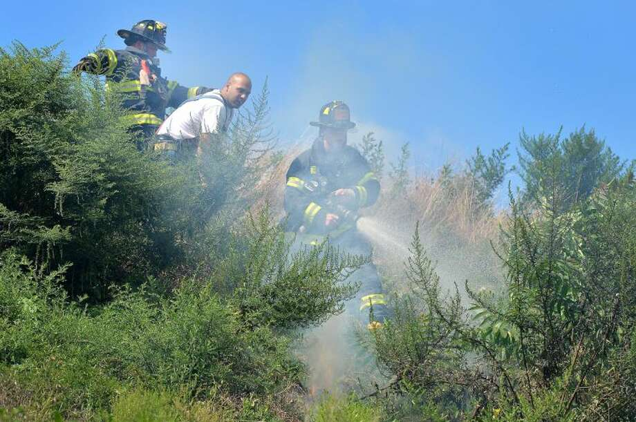 Hour Photo/Alex von Kleydorff . Norwalk Firefighters knock down a brush fire at Oyster Shell Park on Wednesday.