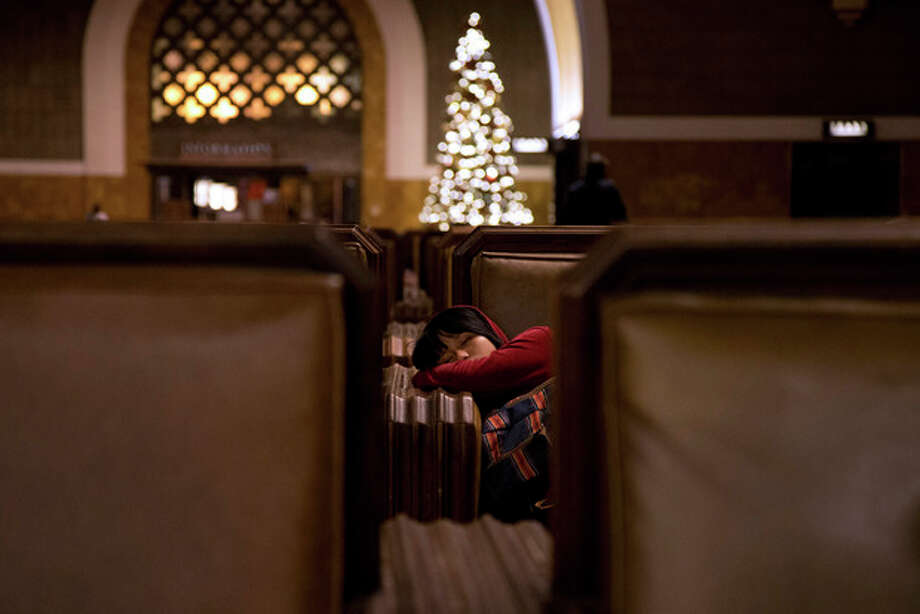 Gelli Ann Dayrit, 19, sleeps while waiting for a bus at Union Station in Los Angeles, Wednesday, Nov. 21, 2012. Feeling the pinch of the sluggish economic recovery, many Americans setting out on the nation's annual Thanksgiving migration had to sacrifice summer vacations, rely on relatives for airfare or scour the Web for travel deals to ensure they made it home. (AP Photo/Jae C. Hong) / AP