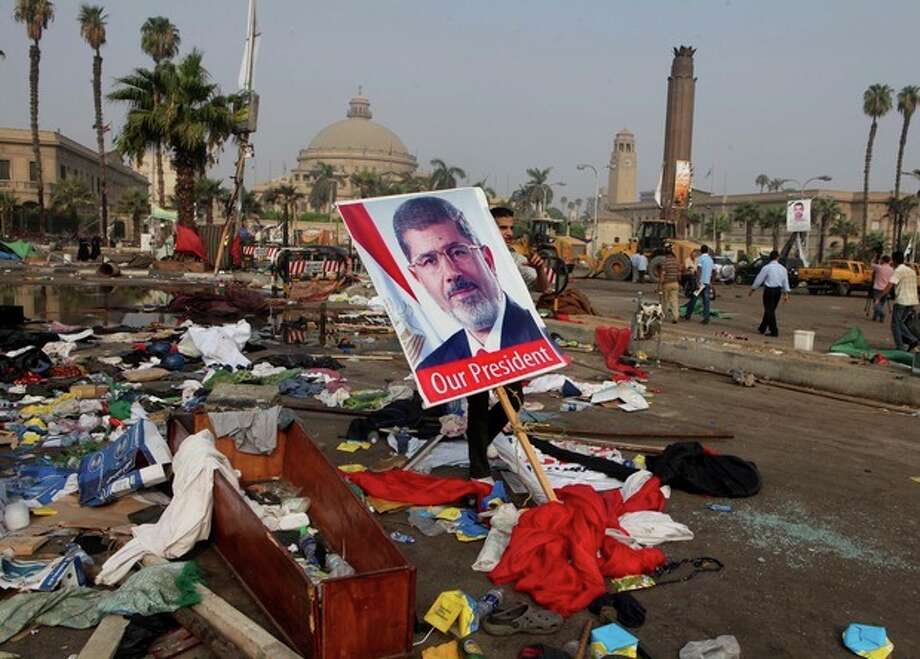 An Egyptian carries a poster of Egypt's ousted President Mohammed Morsi among debris from a protest camp in Nahda Square, Giza, Cairo, Egypt, Thursday, Aug. 15, 2013. Egypt faced a new phase of uncertainty on Thursday after the bloodiest day since its Arab Spring began, with over 300 people reported killed and thousands injured as police smashed two protest camps of supporters of the deposed Islamist president. Wednesday's raids touched off day-long street violence that prompted the military-backed interim leaders to impose a state of emergency and curfew, and drew widespread condemnation from the Muslim world and the West, including the United States. (AP Photo/Amr Nabil) / AP