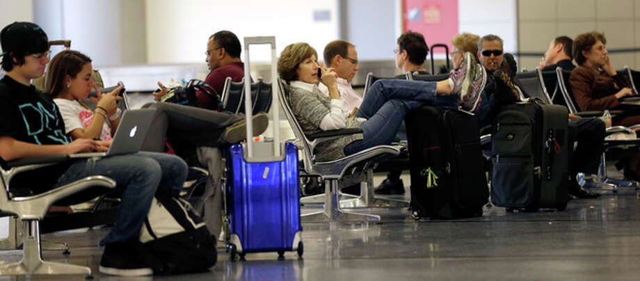Passengers wait in baggage claim at George Bush Intercontinental Airport Tuesday, Nov. 20, 2012, in Houston. Americans can expect airports to be busier and planes to be fuller than ever, according to a forecast by the main trade association for U.S. airlines released ahead of the holiday. (AP Photo/David J. Phillip) / AP