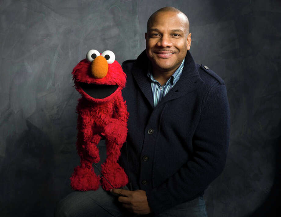 "FILE - In this Jan. 24, 2011 file photo, Elmo puppeteer Kevin Clash poses with the ""Sesame Street"" muppet in the Fender Music Lodge during the 2011 Sundance Film Festival in Park City, Utah. Sesame Workshop says Elmo puppeteer Kevin Clash has resigned from ""Sesame Street"" in the wake of allegations that he had sex with an under-aged youth. Last week a man accused Clash of having sex with him when he was a teenage boy, a charge Clash denied. A day later, the man recanted his charge. A lawsuit by a second accuser was filed Tuesday, Nov. 20, according to attorney Cecil Singleton. (AP Photo/Victoria Will, File) / WILLV"