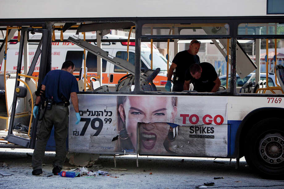 Israeli police officers examine a blown up bus at the site of a bombing in Tel Aviv, Israel, Wednesday, Nov. 21, 2012. A bomb ripped through an Israeli bus near the nation's military headquarters in Tel Aviv on Wednesday, wounding at several people, Israeli officials said. The blast came amid a weeklong Israeli offensive against Palestinian militants in Gaza. (AP Photo/Oded Balilty) / AP