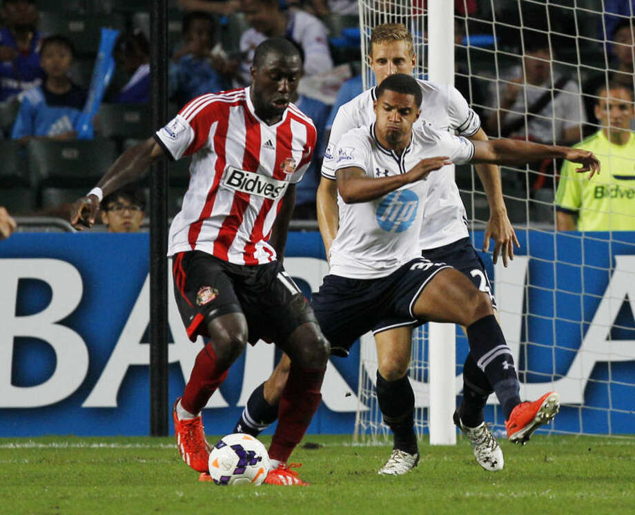 Jozy Altidore of Sunderland, left, controls the ball during the match against Tottenham Hotspur at the Barclays Asia Trophy Wednesday, July 24, 2013. (AP Photo/Kin Cheung)