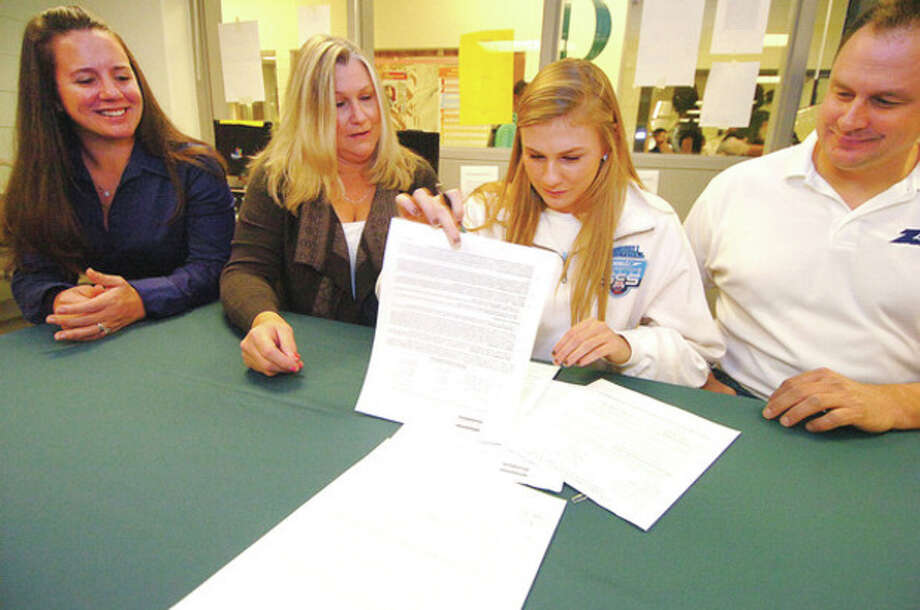 Hour photo/Alex von KleydorffNorwalk swimmer Stephanie Czulewicz, second from right, signs her Letter of Intent to attend Central Connecticut. Watching, from left, are swim coach Rebecca Rubin, Ellie Czulewicz Don Czuliewicz. / 2012 The Hour Newspapers