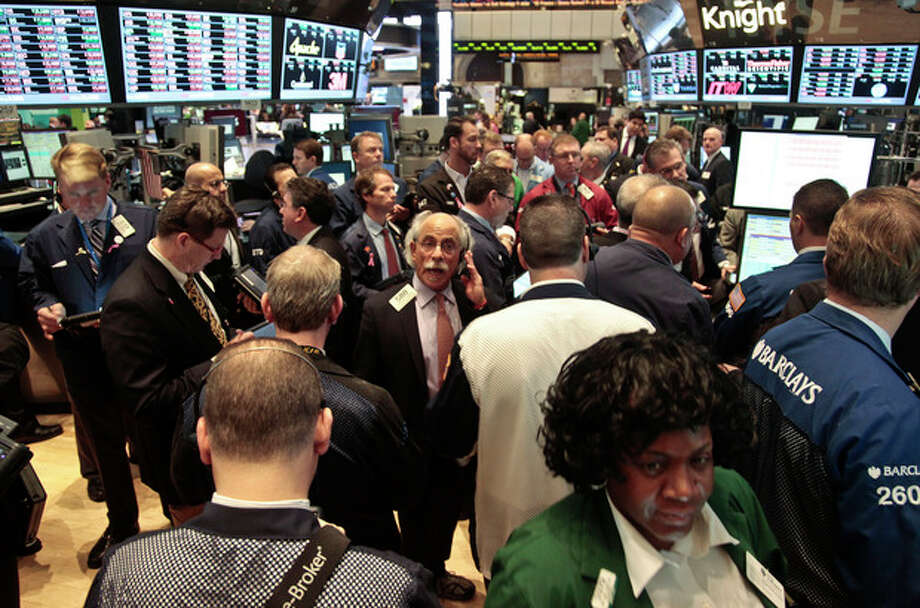 Traders crowd a a Barclays booth during early trading on the floor of the New York Stock Exchange on Tuesday, Nov. 20, 2012. Stocks sank early Tuesday on Wall Street. Hewlett-Packard stock suffered a big decline after its executives said that a company HP bought for $10 billion last year lied about its finances. (AP Photo/Bebeto Matthews) / AP