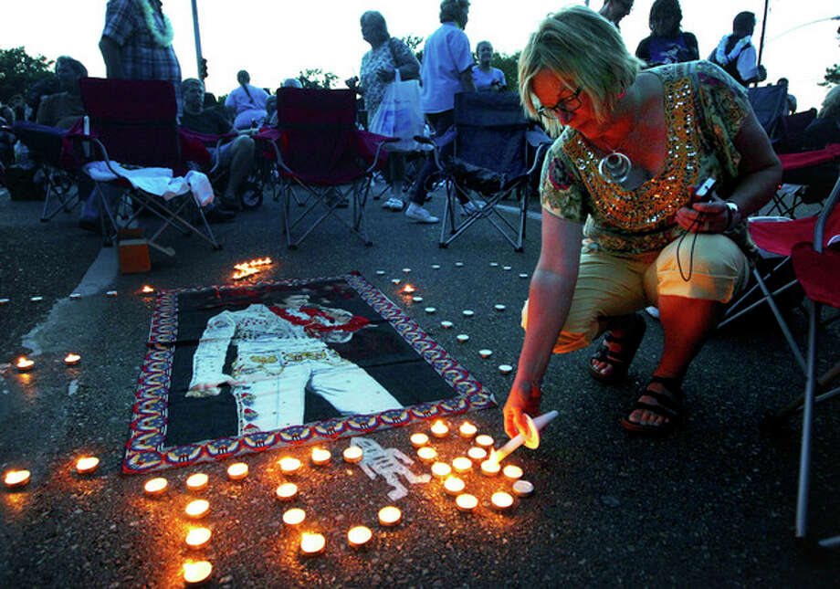 Elvis Presley fan Jill Gibson lights candles outside Graceland, Presley's home, before the annual candlelight vigil on Thursday, Aug. 15, 2013, in Memphis, Tenn. Presley fans from around the world made their annual pilgrimage to Graceland to pay their respects to the rock n' roll icon with a solemn candlelight vigil on the 36th anniversary of his death. (AP Photo/The Commercial Appeal, Nikki Boertman) / The Commercial Appeal