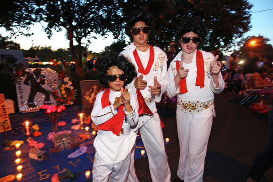 Nicholas Woodlief, 7, left, his sister Annabelle Woodlief, 11, and friend, Eli Crain, 11, right, strike an Elvis Presley pose at Graceland, Presley's home, before the annual candlelight vigil on Thursday, Aug. 15, 2013, in Memphis, Tenn. Presley fans from around the world made their annual pilgrimage to Graceland to pay their respects to the rock n' roll icon with a solemn candlelight vigil on the 36th anniversary of his death. (AP Photo/The Commercial Appeal, Nikki Boertman) / The Commercial Appeal