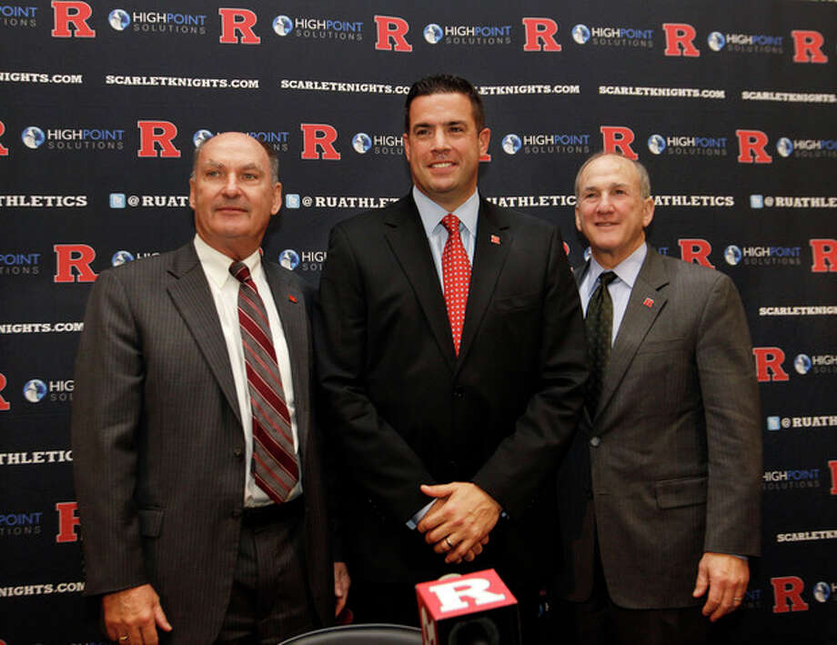 Rutgers Director of Intercollegiate Athletics Tim Pernetti, center, stands with Rutgers President Robert Barchi, right, and Big Ten Conference Commissioner Jim Delany during a news conference, Tuesday, Nov. 20, 2012, in Piscataway, N.J., after they announced that Rutgers will join the Big Ten. Rutgers will join the conference in all sports at a date to be determined. (AP Photo/Mel Evans) / AP