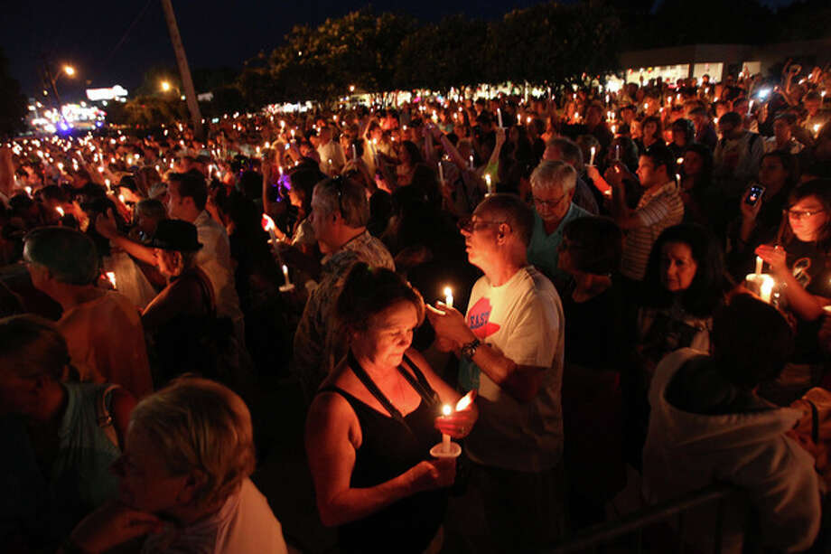 Fans of the late Elvis Presley gather at Graceland, Presley's home, for the annual candlelight vigil on Thursday, Aug. 15, 2013, in Memphis, Tenn. Presley fans from around the world made their annual pilgrimage to Graceland to pay their respects to the rock n' roll icon with a solemn candlelight vigil on the 36th anniversary of his death. (AP Photo/The Commercial Appeal, Nikki Boertman) / The Commercial Appeal