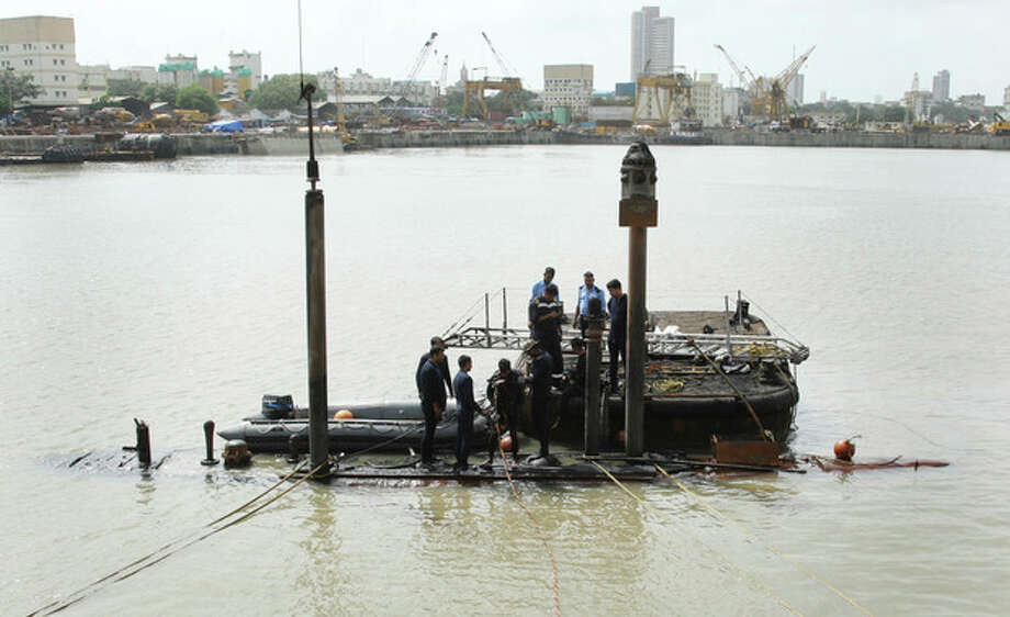 In this Wednesday, Aug. 14, 2013 photo released by the Indian Navy, Indian navy personnel inspect a Russian-made submarine, INS Sindhurakshak, at a naval dockyard where it caught fire and sank after twin explosions in Mumbai, India. Indian navy divers on Friday, Aug. 16, recovered three severely burned bodies of sailors who had been trapped inside the submarine, a navy spokesman said. He added that it was doubtful that any of the other 15 sailors aboard survived. (AP Photo/Indian Navy) / Indian Navy