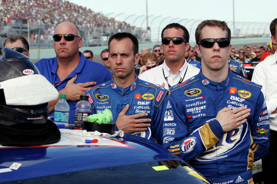 Brad Keselowski and members of his crew listen to the national anthem before the NASCAR Sprint Cup Series auto race at Homestead-Miami Speedway, Sunday, Nov. 18, 2012, in Homestead, Fla. (AP Photo/The Miami Herald, Andrew Uloza) MAGS OUT / The Miami Herald
