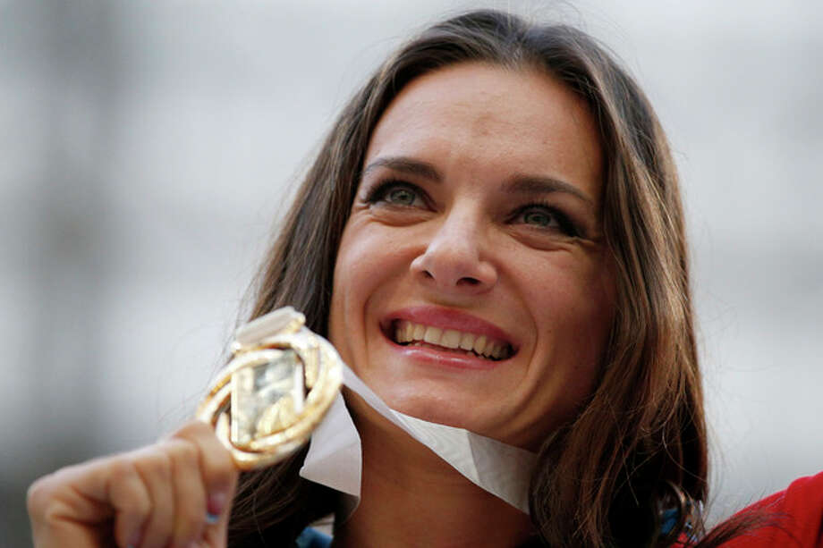 Russia's Yelena Isinbayeva poses with her gold medal in the women's pole vault as she stands on the podium during the medal ceremony at the World Athletics Championships in the Luzhniki stadium in Moscow, Russia, Thursday, Aug. 15, 2013. (AP Photo/Alexander Zemlianichenko) / AP