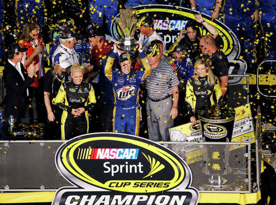 Brad Keselowski, center, holds up his trophy after winning the NASCAR Sprint Cup Series championship following an auto race at Homestead-Miami Speedway, Sunday, Nov. 18, 2012, in Homestead, Fla. Keselowski clinched the title after fellow contender Jimmie Johnson pulled out of the season finale because of a parts failure. Jeff Gordon won the race. (AP Photo/Wilfredo Lee) / AP
