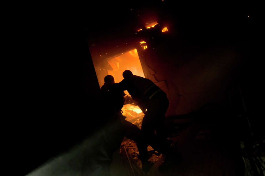 Palestinians firefighters try to extinguish a fire after an Israeli strike on a building of Gaza City, Monday, Nov. 19, 2012. Palestinian militant group Islamic Jihad says an Israeli strike on a Gaza media center has killed one of its top militant leaders. (AP Photo/Bernat Armangue) / AP