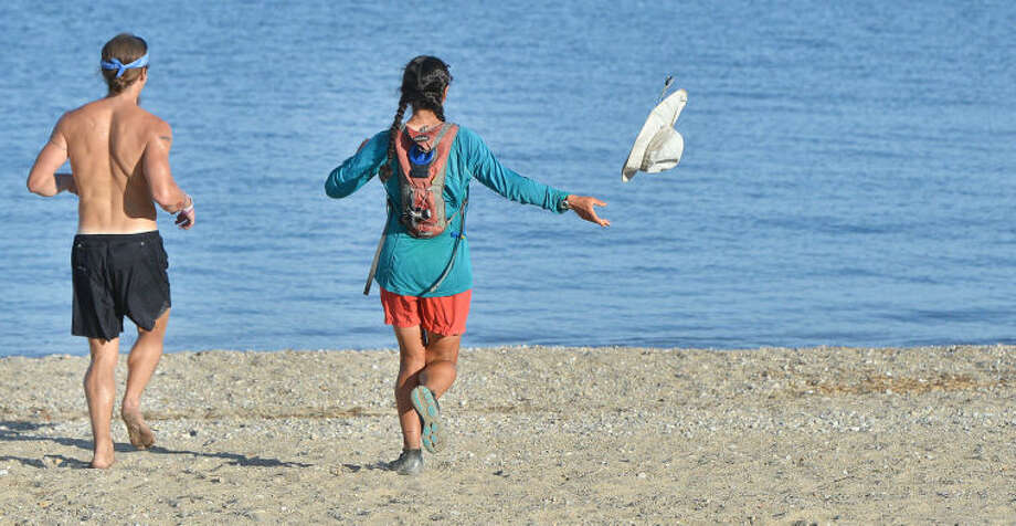 Hour Photo/Alex von Kleydorff . Heading for the water with her running partner Jake Brown as fast as possible throwing her hat, Rosalynn Frederick finishes a 3000 mile run/walk accros the country