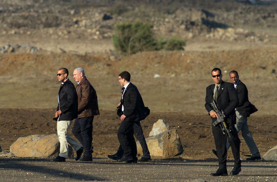 FILE- In this Nov. 14, 2012, file photo, Israeli Prime Minister Benjamin Netanyahu, second left, is surrounded by bodyguards as he walks towards a military helicopter following a visit to the Golan Heights. After seven years in power, Natanyahu has pulled the trigger, unleashing a massive offensive against Gaza rocket-launchers. The public and even his political opponents have all lined up behind him and barring a fiasco involving heavy Israeli casualties, Netanyahu should coast to victory in the upcoming Israeli elections. (AP Photo/Hamad Almakt, File) / AP