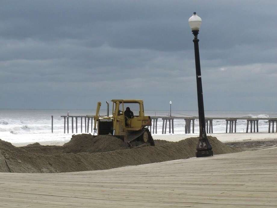 A bulldozer pushes piles of sand around on the Ocean Grove N.J. beach in front of its storm-buckled boardwalk and damaged fishing pier on Nov. 15, 2012. Superstorm Sandy took a bite out of the Jersey shore, washing away millions of tons of sand and slimming down beaches along the state's 127-mile coastline. (AP Photo/Wayne Parry) / AP