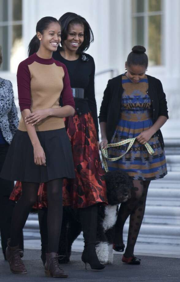 First lady Michelle Obama, with daughters Sasha and Malia, left, and first dog Bo, walk on the North Portico of the White House in Washington, Friday, Nov. 23, 2012, where they received the official White House Christmas tree, a 19-foot Fraser Fir from Jefferson, N.C. (AP Photo/Manuel Balce Ceneta)