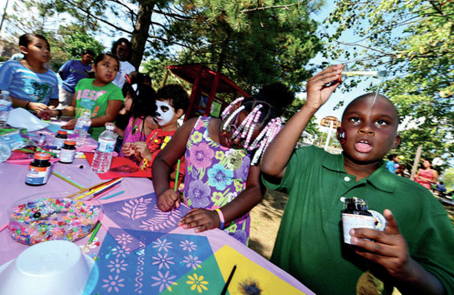 Hour photo / Erik TrautmannEight-year-old Taquan Gene Louis works on a craft during the SoNo Day Out held by Norwalk Police Department at Ryan Park Saturday. / (C)2013, The Hour Newspapers, all rights reserved