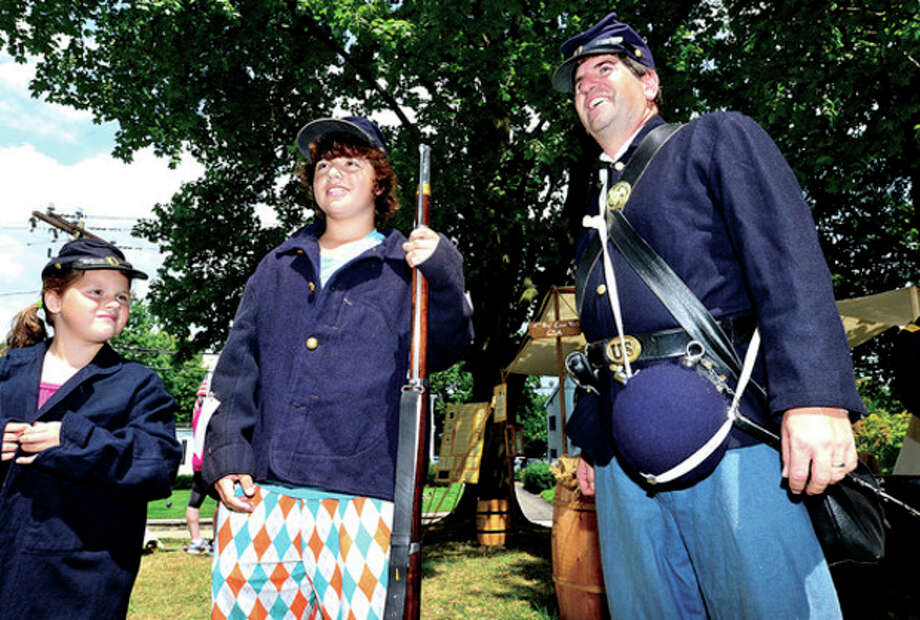 Julia and Colin Bella, 7 and 12, tryon a military uniform with the help of David Fuda, a reenactor with the 11th regiment of the CT Volunteer Infantry, as The Norwalk Historical Society hosts the third annual Civil War BBQ and Encampment at Mill Hill Historic Park Saturday.Hour photo / Erik Trautmann / (C)2013, The Hour Newspapers, all rights reserved