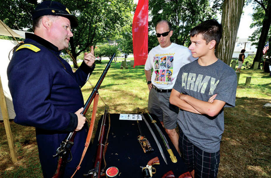 Devin Piercey and Mike Tamborrino listen to John Tuchick, a reenactor with the 11th regiment of the CT Volunteer Infantry, explain his weapory as The Norwalk Historical Society hosts the third annual Civil War BBQ and Encampment at Mill Hill Historic Park Saturday.Hour photo / Erik Trautmann / (C)2013, The Hour Newspapers, all rights reserved