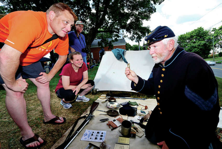 Norwalk residents Fred and Carla Fishman listen to Martin Schmidt, a reenactor with the 11th regiment of the CT Volunteer Infantry, explain his gear as The Norwalk Historical Society hosts the third annual Civil War BBQ and Encampment at Mill Hill Historic Park Saturday.Hour photo / Erik Trautmann / (C)2013, The Hour Newspapers, all rights reserved