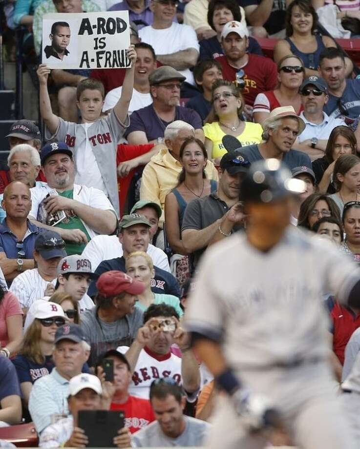 A young fan holds a sign while New York Yankees' Alex Rodriguez, bottom right, bats in the eighth inning of a baseball game against the Boston Red Sox in Boston, Saturday, Aug. 17, 2013. (AP Photo/Michael Dwyer)
