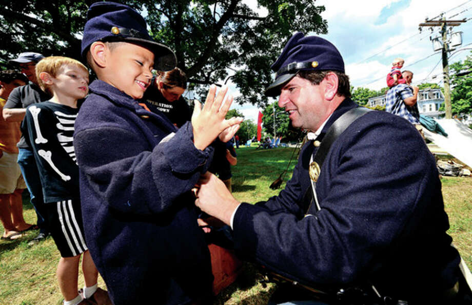 6 year old Zachary Ruiz tries on a military uniform with the help of David Fuda a reenactor with the 11th regiment of the CT Volunteer Infantry as The Norwalk Historical Society hosts the third annual Civil War BBQ and Encampment at Mill Hill Historic Park Saturday.Hour photo / Erik Trautmann / (C)2013, The Hour Newspapers, all rights reserved