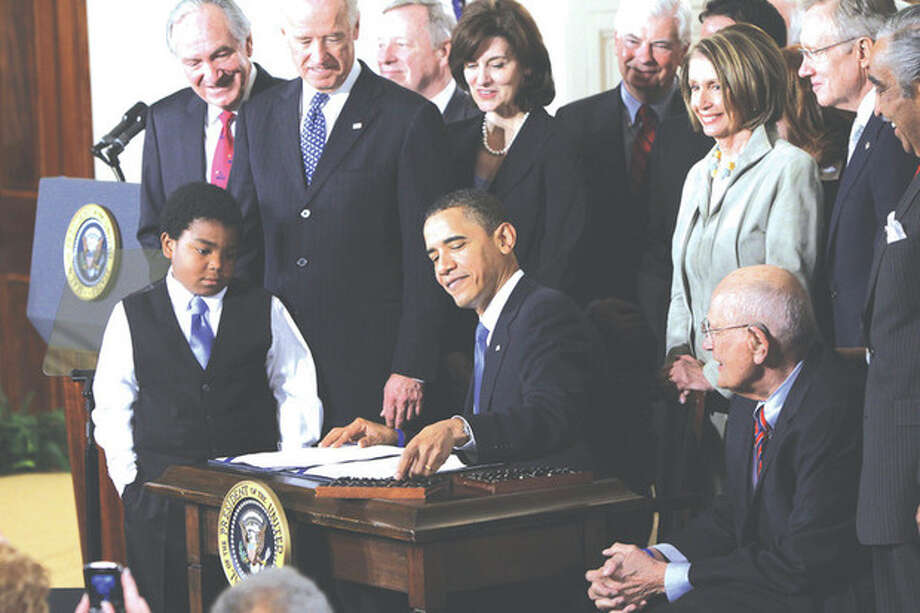 AP file photo / Charles DharapakIn this March 23, 2010, file photo, President Barack Obama reaches for a pen to sign the health care bill in the East Room of the White House in Washington. Obama's re-election has guaranteed the survival of his health care law. / AP