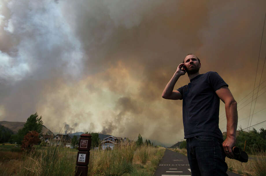 Kevin Bullock, of Bellevue, Idaho, watches smoke from the 64,000 acre Beaver Creek Fire on Friday, Aug., 16, 2013 north of Hailey, Idaho. A number of residential neighborhoods have been evacuated because of the blaze.(AP Photo/Times-News, Ashley Smith) MANDATORY CREDIT / The Times-News