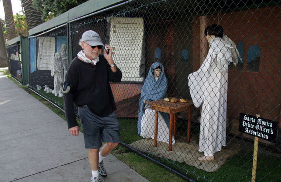 """FILE - In this Dec. 13, 2011 file photo, a man walks past two of the traditional Nativity scenes along Ocean Avenue at Palisades Park in Santa Monica, Calif. Avowed atheist Damon Vix last year won two-thirds of the booths in the annual, city-sponsored lottery to divvy up spaces in the live-sized Nativity display. But he only put up one thing: A sign that read """"Religions are all alike - founded on fables and mythologies."""" Vix left the rest of his allotted spaces empty, and in so doing, upended a Christmas tradition that began in Santa Monica nearly 60 years ago. (AP Photo/Ringo H.W. Chiu, file) / FR170512 AP"""