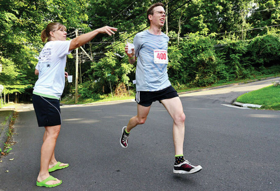 Hour photo/Erik TrautmannVolunteer Allicia Clark passes water to race winner Daniel Lennox during the Lightfoot Running Club's fifth race of the season Saturday at Silvermine Elementary School. / (C)2013, The Hour Newspapers, all rights reserved