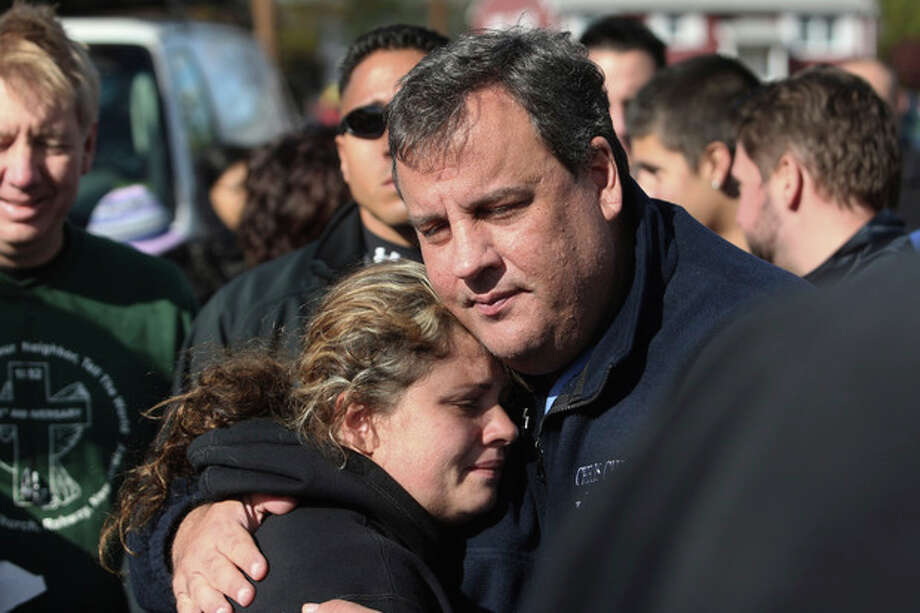 FILE - In this Nov. 3, 2012 file photo, New Jersey Gov. Chris Christie comforts Kerri Berean in Little Ferry, N.J., after Superstorm Sandy caused a tidal surge on the Hackensack River that overtook a natural berm protecting the town. For Christie, leadership after Sandy often came with an empathetic hug. For New York Gov. Andrew Cuomo, it came with an angry tirade at utilities slow to restore power. For New York City Mayor Michael Bloomberg, it came with cool, businesslike assurance. (AP Photo/The Star-Ledger, David Gard, Pool, File) / Pool The Star-Ledger