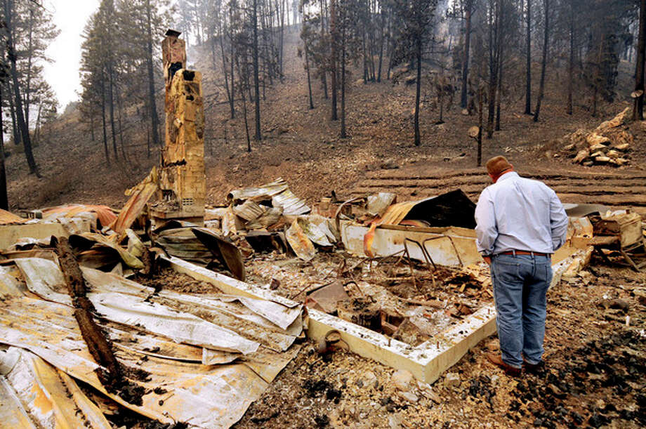 U.S. Sen. Jon Tester, D-Mont., looks at the remains of a Lolo Creek home that was destroyed by the West Fork II fire when it swept down the Lolo Creek canyon, Wednesday, Aug. 21, 2013 near Lolo, Mont. The fire burned four other homes as well along the U.S. Highway 12 corridor. (AP Photo/Missoulian, Kurt Wilson) / The Missoulian